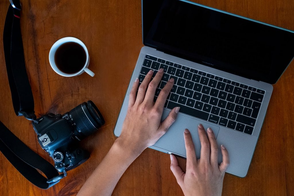 A womans hands typing on a computer with a coffee and a camera next to her on a table demonstrating Lightroom presets and how to install them.