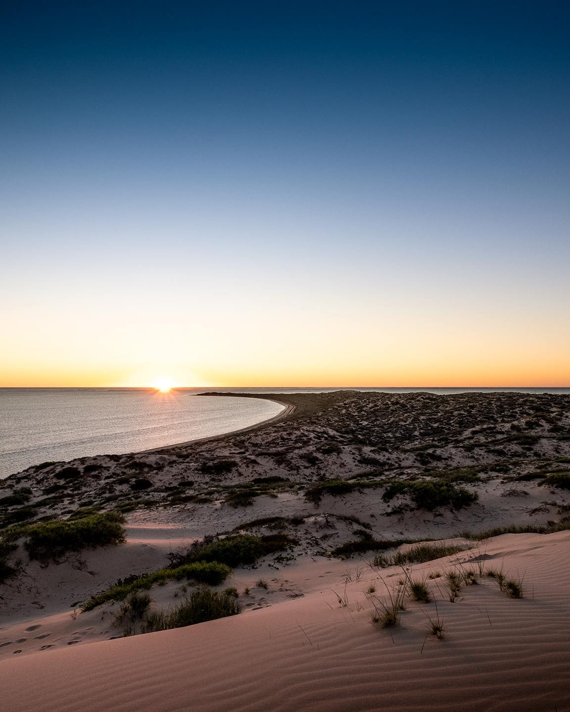 Looking out to sea with a coastline that curves round to the left as the perfect sunset light hits sandy dunes in the foreground.