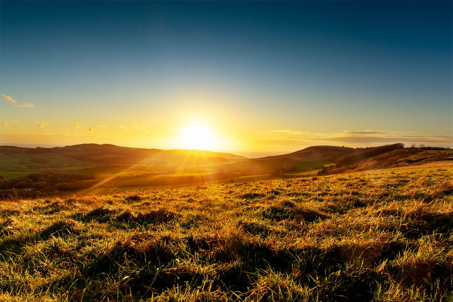 A perfect sunset looking straight towards the setting sun with a large grassy hill that leads towards the sea.