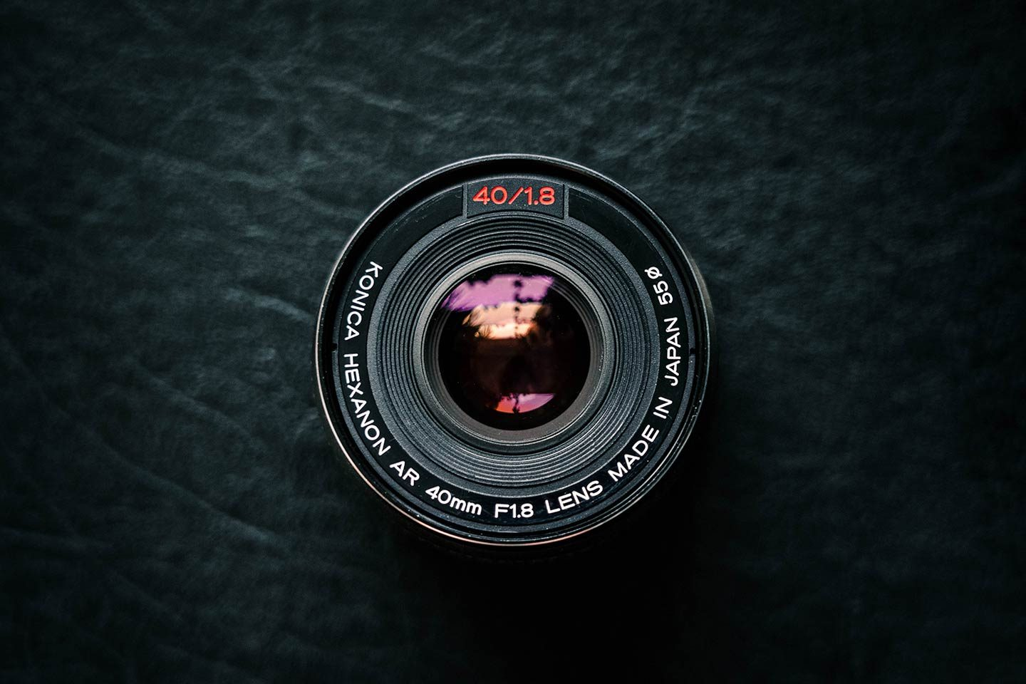 The front of a 40mm lens on a black textured background