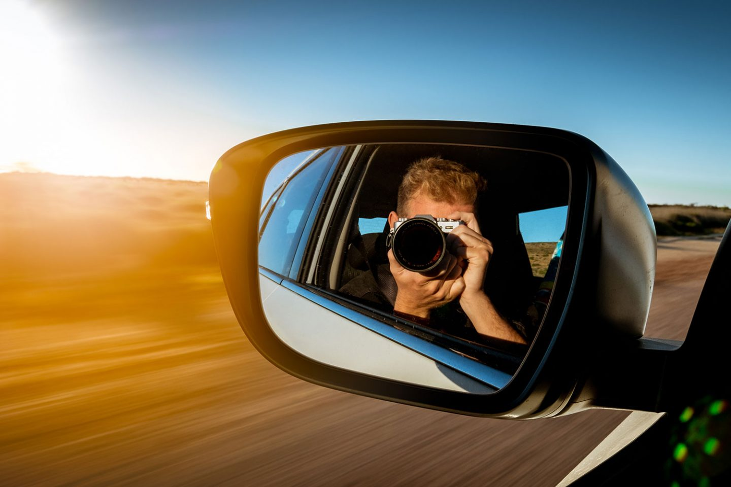 Man taking a photo of himself in a car mirror as car is driving with the warm bright light of the sunset hits the car mirror