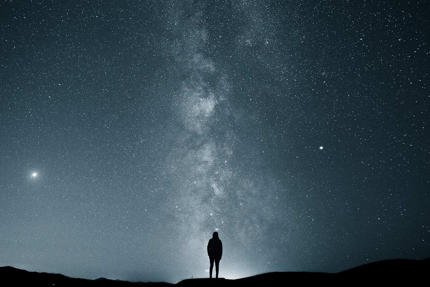 A silhouette of a man looking out to the vastness of the Milky Way on a clear night when the sky is lit up with stars. If you're looking for the best astrophotography camera low light performance is very important.