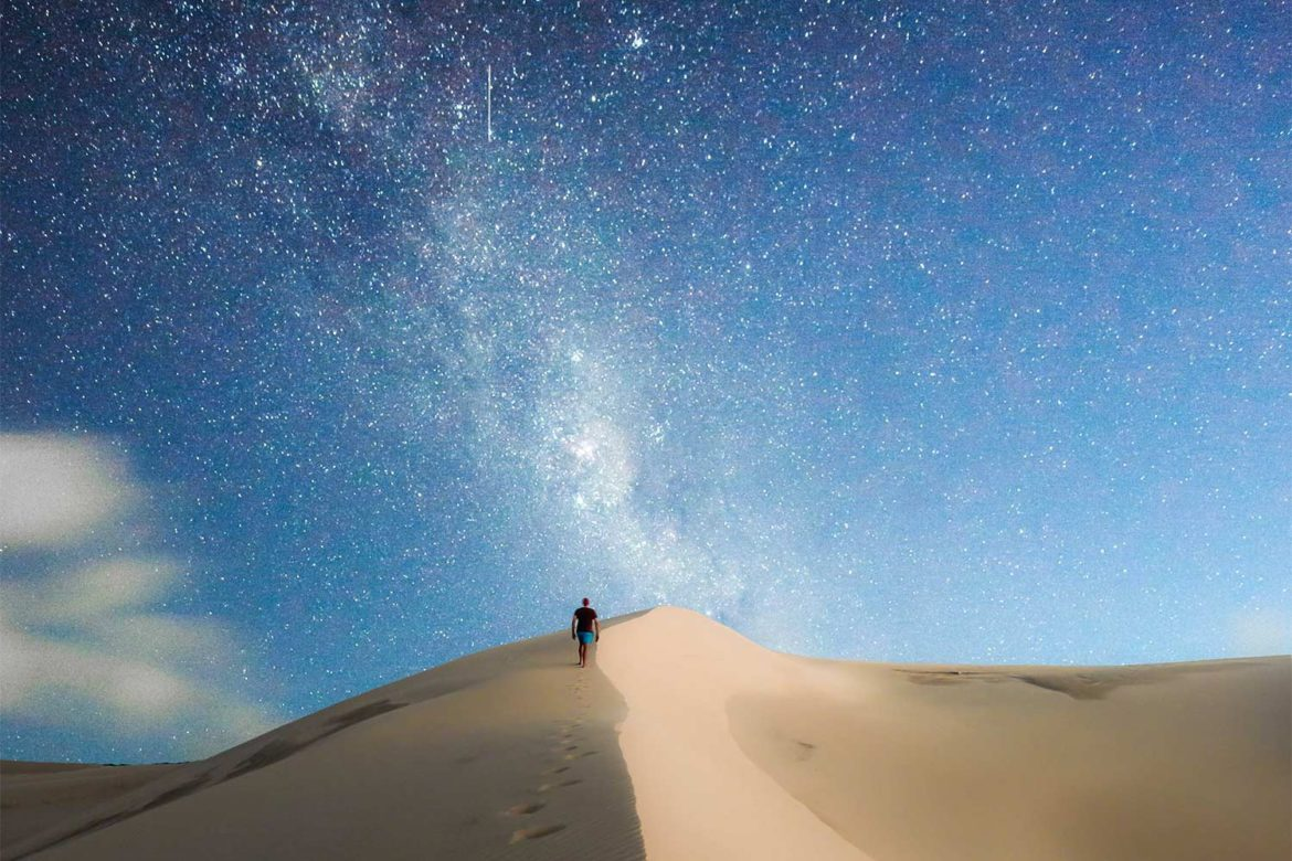 A man walks along sand dunes at night towards the Milky Way that lights up the night sky.