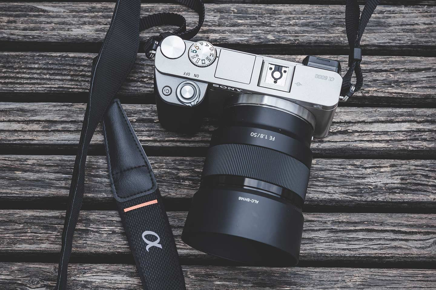 A Sony mirrorless camera on top of a wooden background. Sony's range of mirrorless cameras are a great choice if you're looking for the best camera for astrophotography.