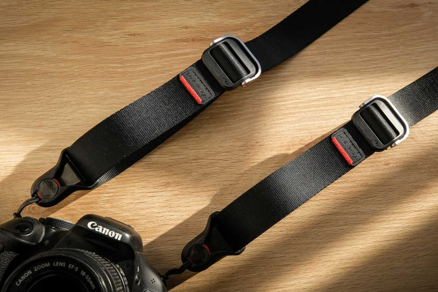 The Peak Design Slide Lite camera strap attached to a camera which is laid down on a desk. One of the must-have photography accessories you need to take with you next time you travel.