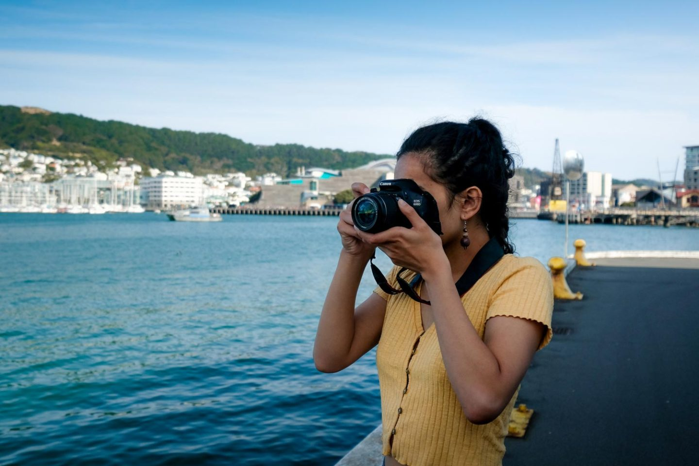 A young women taking a photo with a camera while she travels around the world. Someone who could benefit from this list of must-have photography accessories.