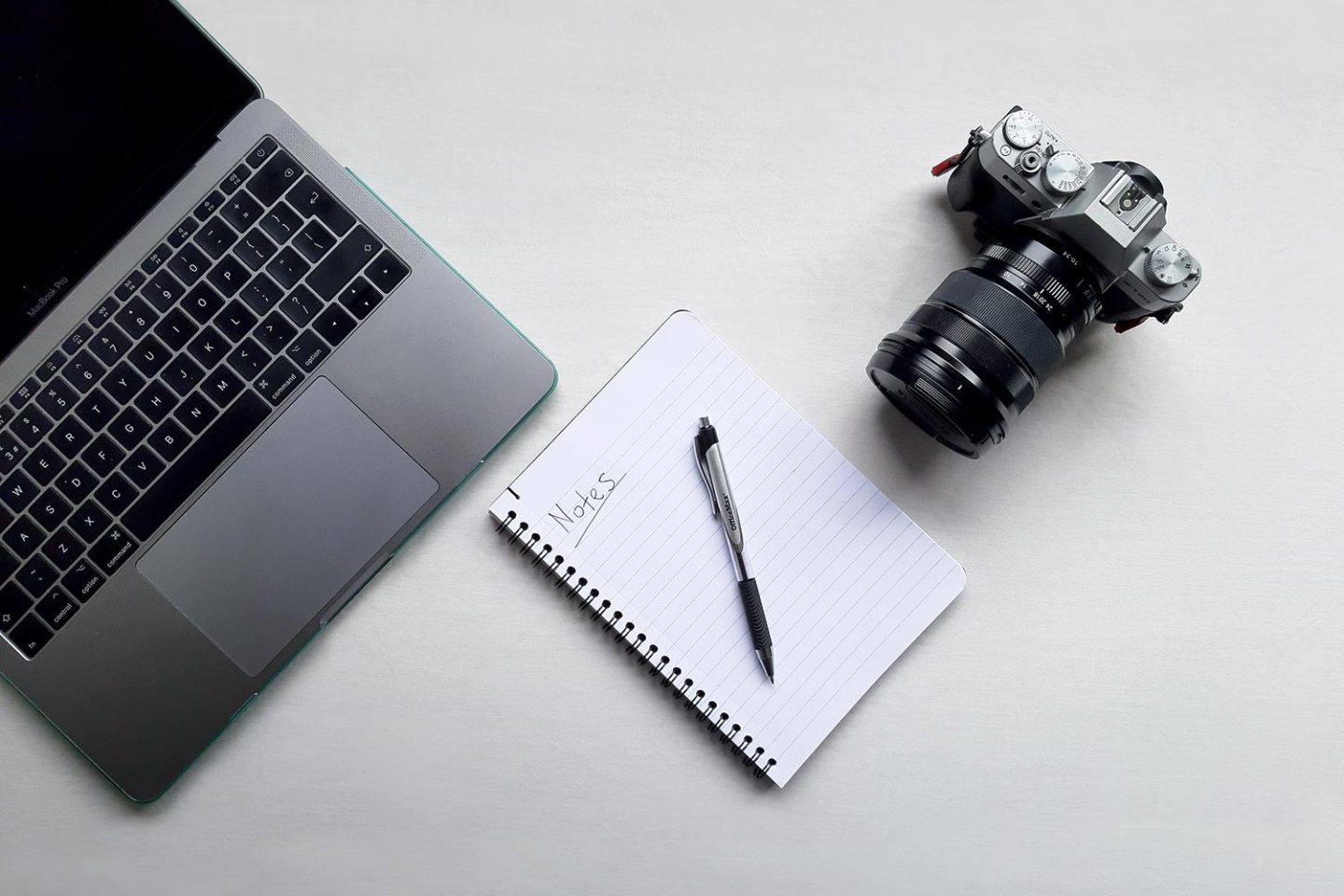 A camera, notepad and laptop arranged on top of a white desk