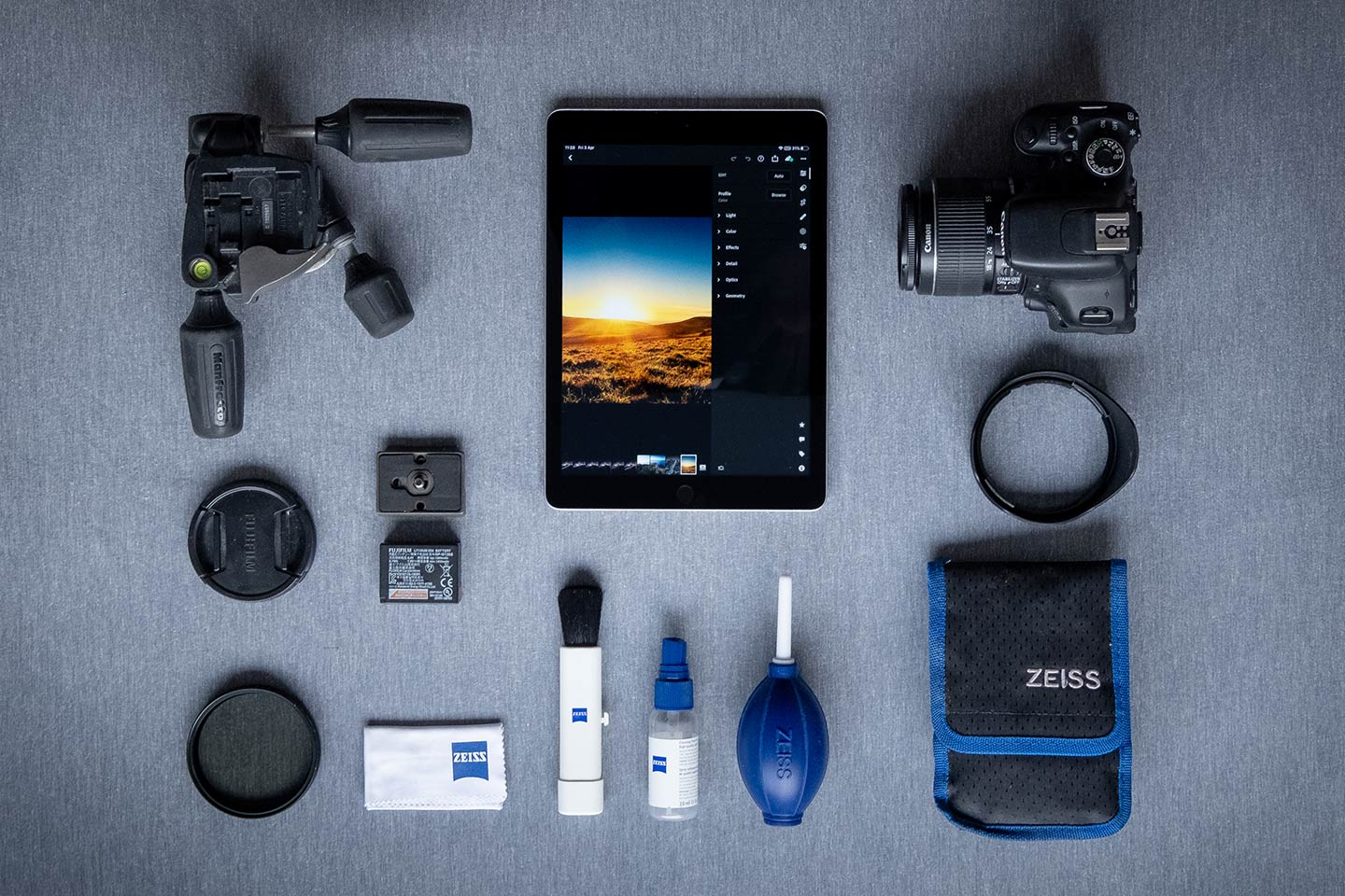 A photography starter kit is laid out on a grey worktop including a camera, iPad, tripod head and cleaning accessories.