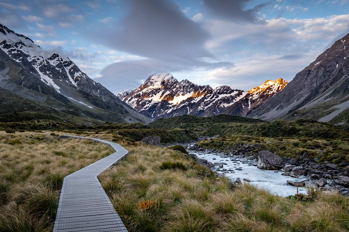 A photo of a New Zealand landscape, in the photo we see a wooden path leading towards a beautiful set of mountains. With the use of travel photography courses photographers can learn to take beautiful photos like this.