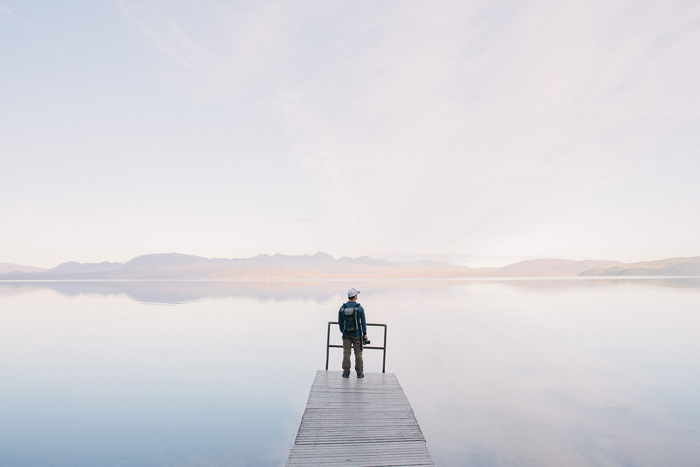 A landscape photographer stands at the end of a jetty looking out at a beautiful lake in front of him.