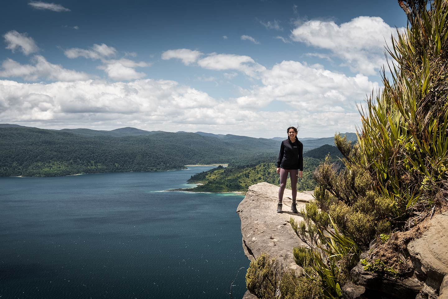A woman standing on Panekire bluff with a large lake behind her.