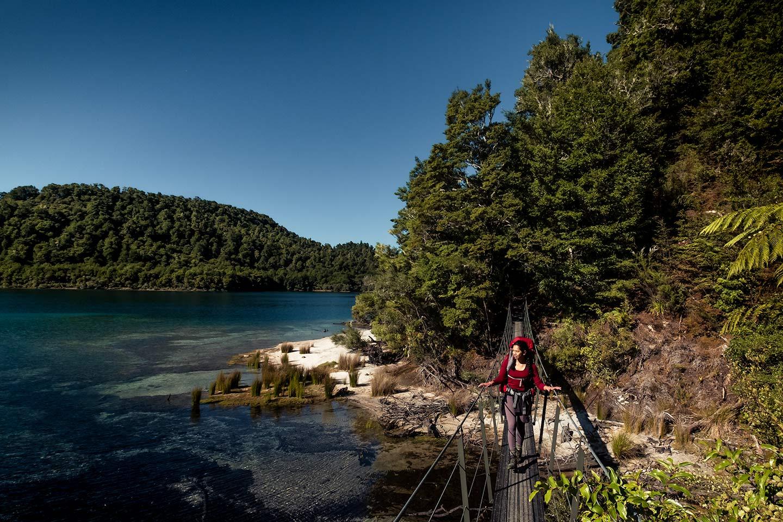 A woman crosses a swing bridge on the Lake Waikaremoana Great Walk.