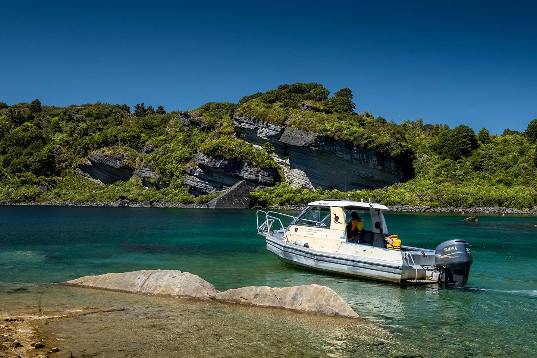 A water taxi speedboat a the edge of a lake on the Lake Waikaremoana Great Walk.