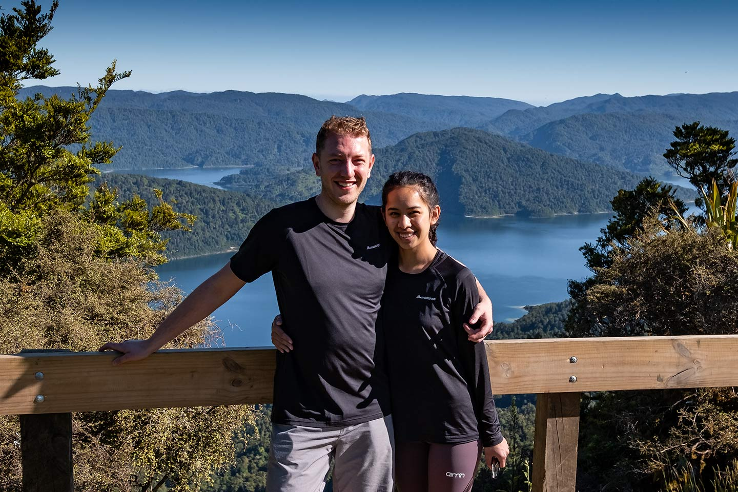 A man and woman photographed with a lake in the background. This photo was taken at Panekire hut on the Lake Waikaremoana Great Walk
