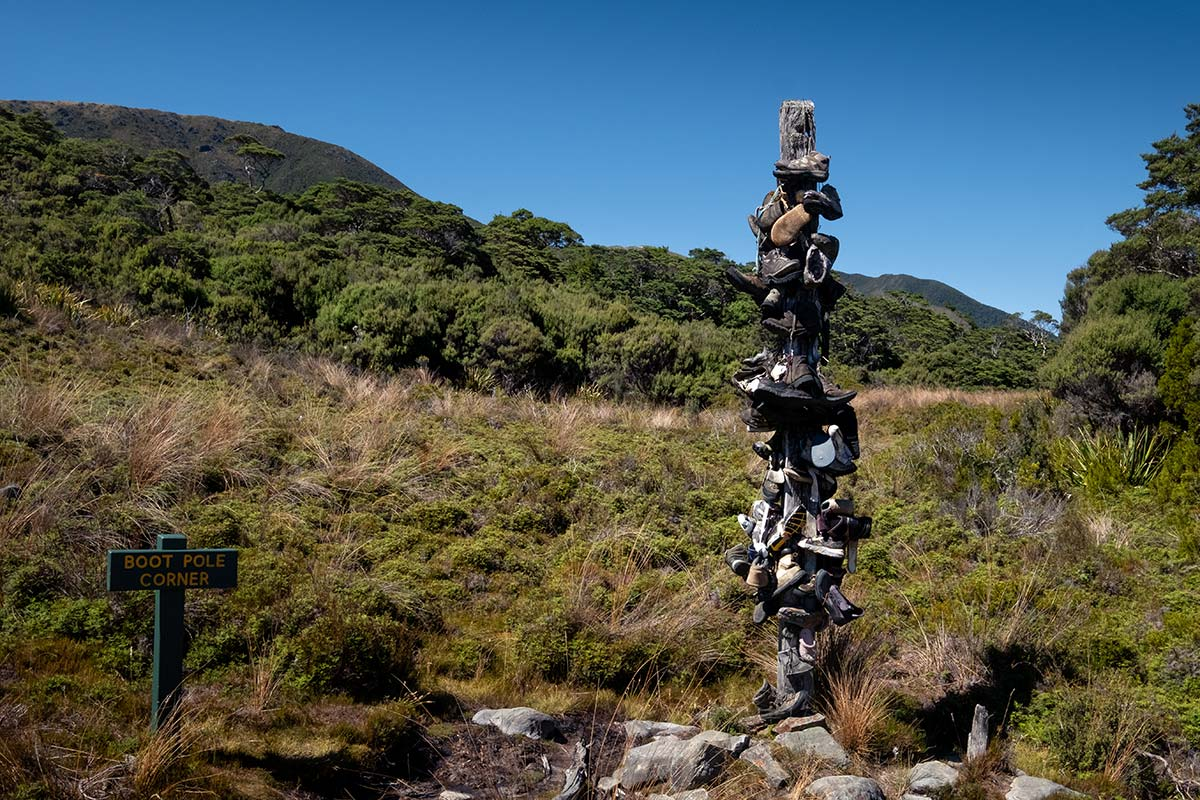 A pole stands high with lots of old walking boots attached to it. This is boot pole corner found on the Heaphy Track.