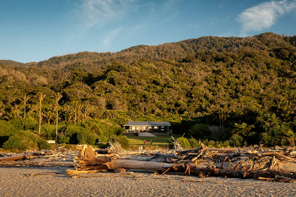 A hut positioned between the tropical trees behind it and a sandy beach in front. This is the Heaphy Hut on the Heaphy Track.