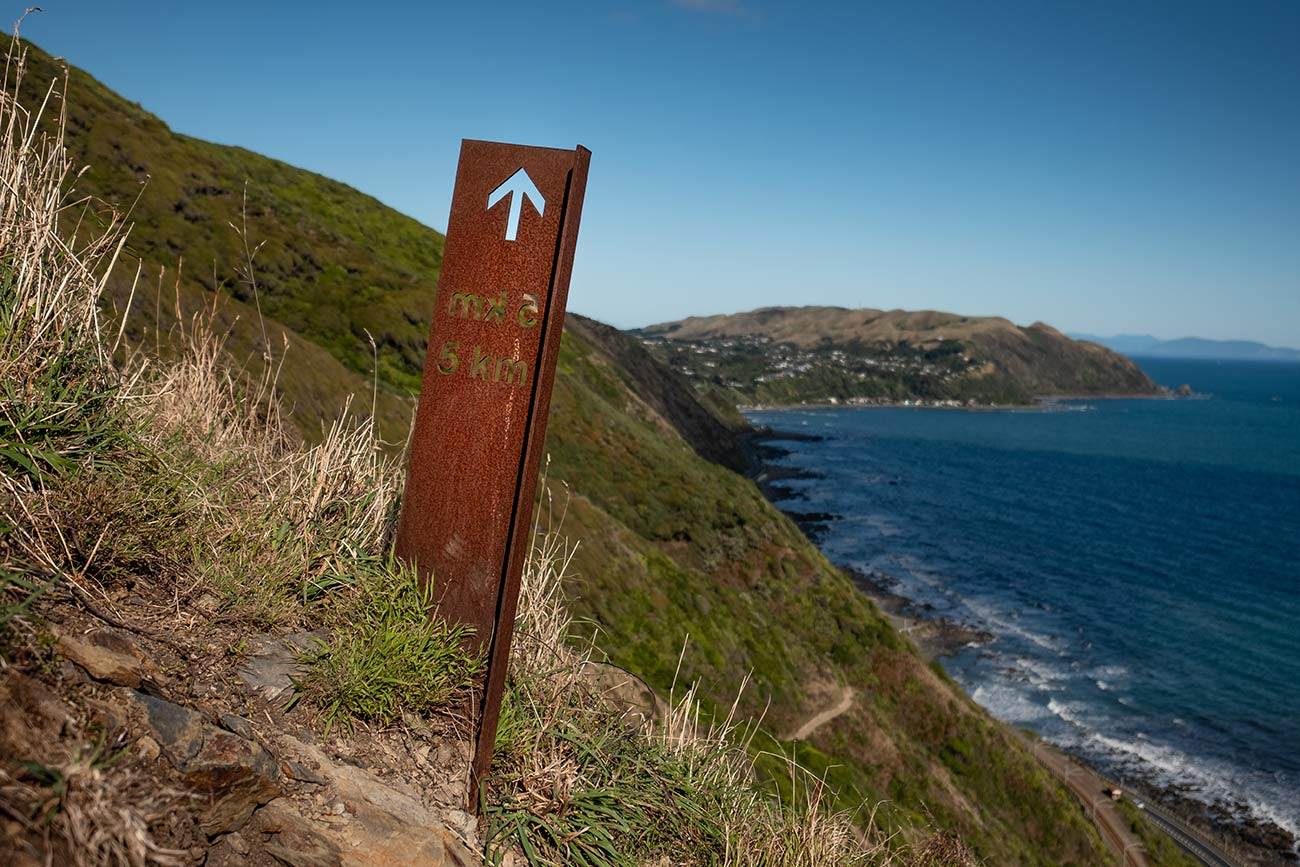 A large rusty 5km marker juts out of the land on the Paekakariki Escarpment track. In the distance the ocean can be seen.