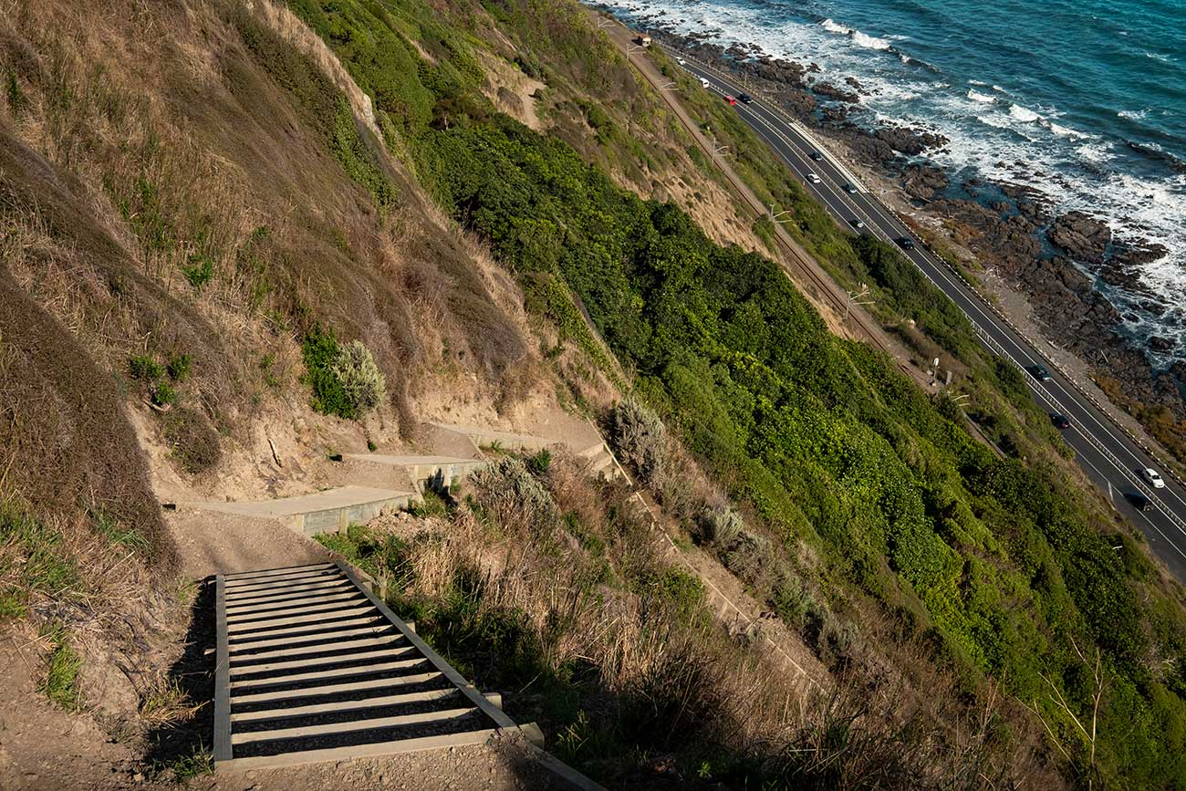 A series of steps constructed into the side of a hill travels down. At the bottom a road is visible next to the ocean.