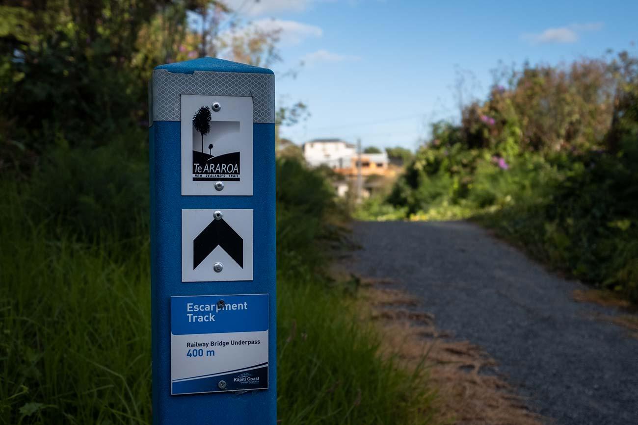 A blue signpost shows the direction to the Te Araroa trail and the start of the Paekakariki Escarpment track.