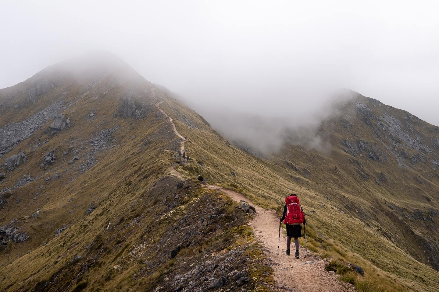 A woman walks along an exposed ridge line on the Kepler Track towards clouds that cover the path in front of her.