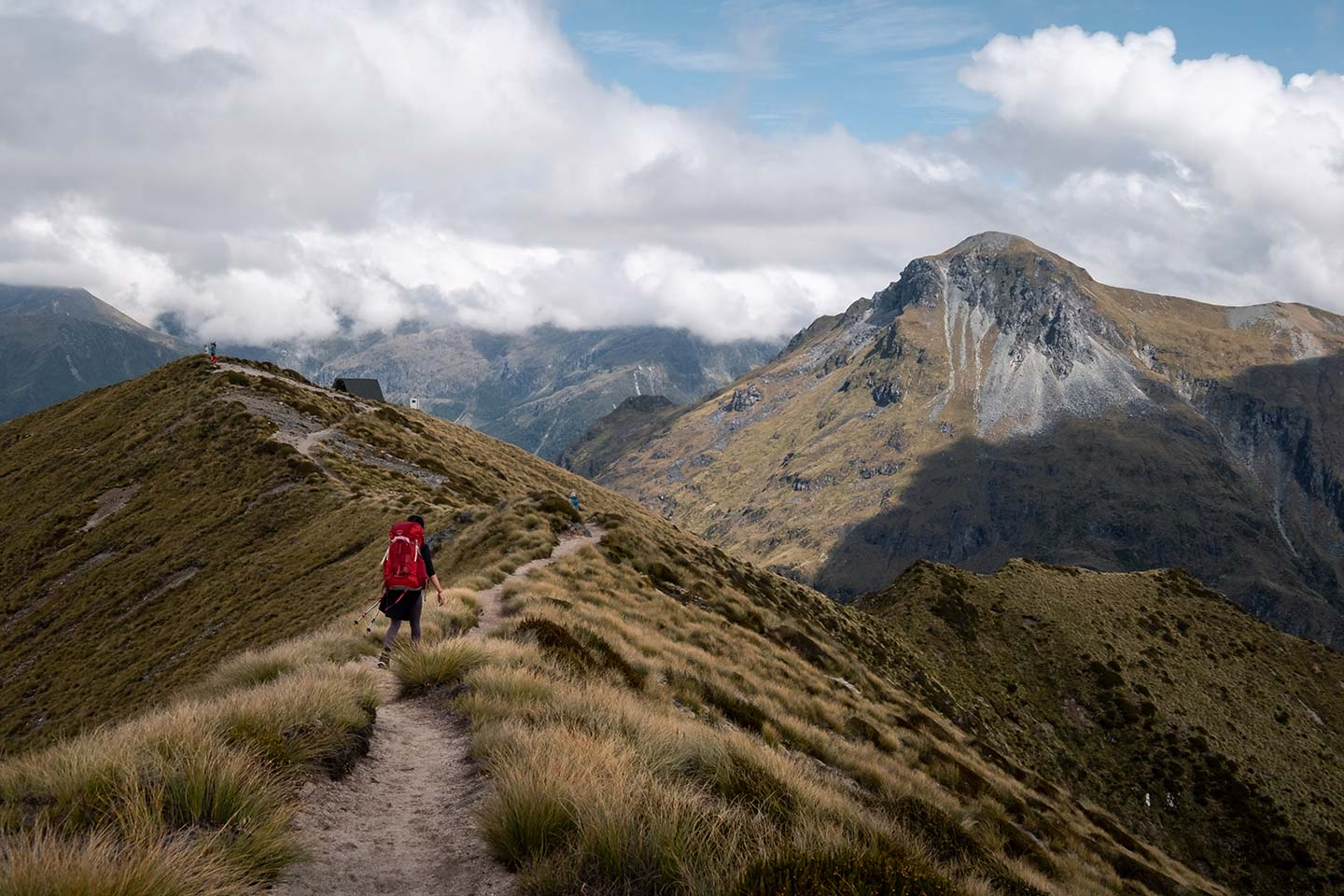 A woman with a large red backpack walks along a ridge line on the Kepler Track, in front of her are large mountains.