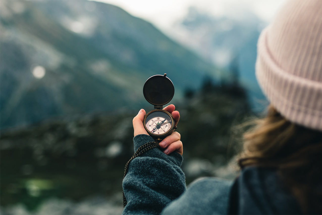 A women holds a compass in front of a mountain range. Add a compass to your day hike packing list in case you get lost.