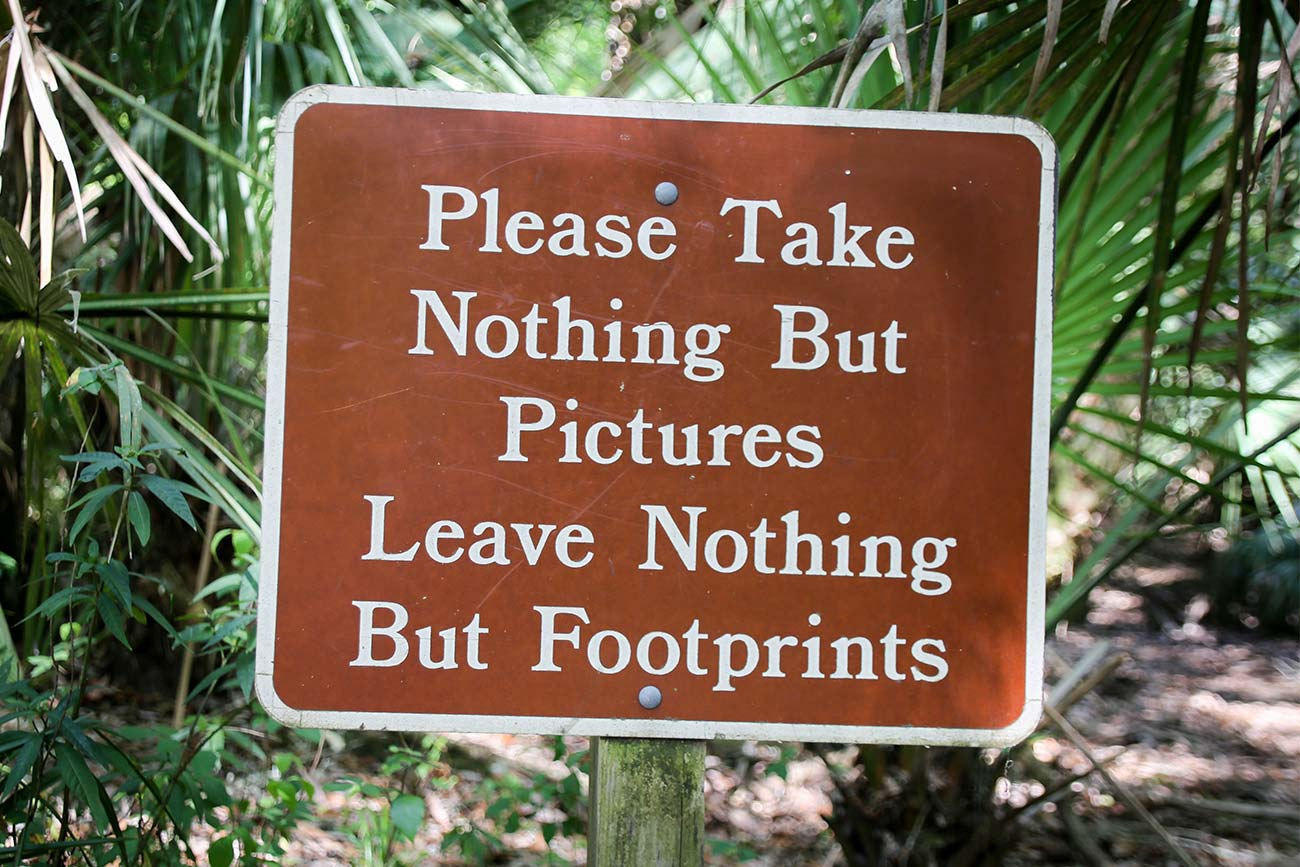 """A brown sign pictured amongst trees. The sign reads """"Please take nothing but pictures, leave nothing but footprints."""""""