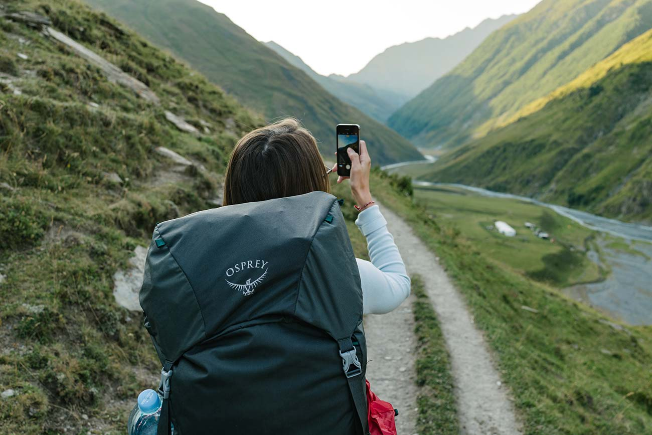 A woman hiking in the wilderness through valleys. She is taking photos using her smartphone. A phone can be useful to have on your day hike packing list especially if you get lost.