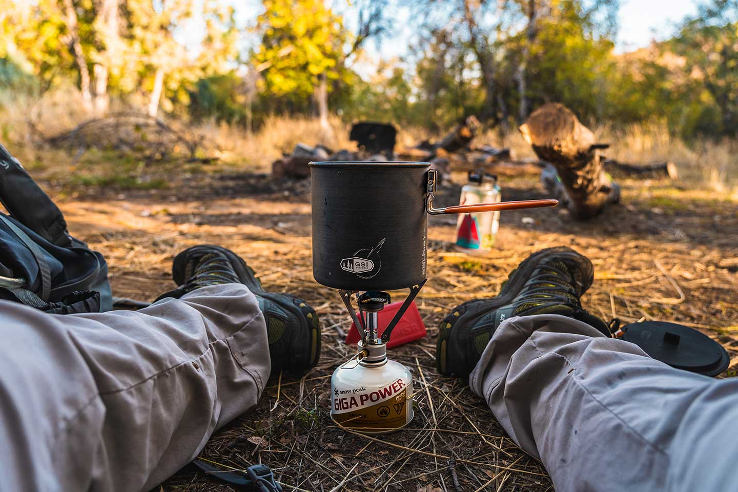 A backpacking stove cooking some vegan backpacking food with camp in the background.