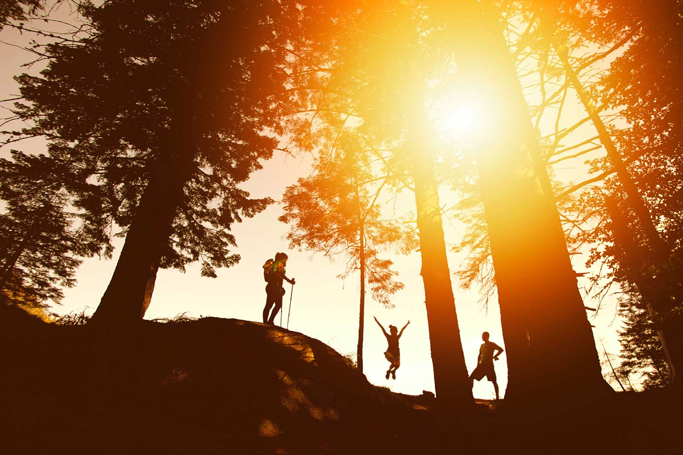 A few friends hiking on a hill with the golden sun behind them. One is jumping in joy.
