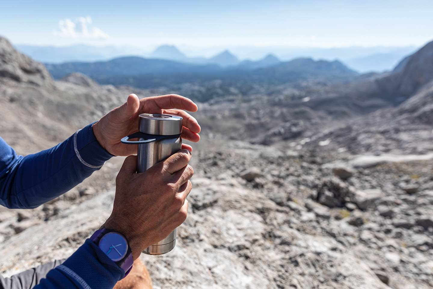 A person screws the lid off of a metal water bottle out in a rocky and rugged landscape.