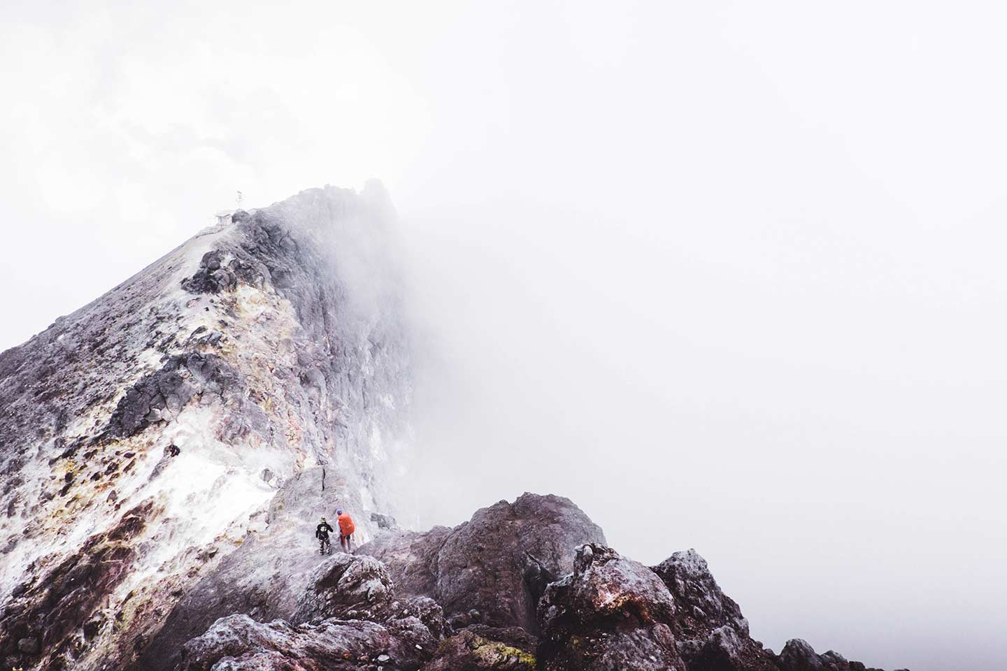 A ridge line of a mountain shows through a thick layer of clouds.  Two people can be seen walking along the ridge line.