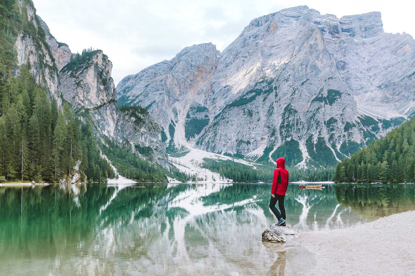 A man in a road coat stands on a rock next to a crystal clear lake.  Surrounding the lake are beautiful rocky mountains.